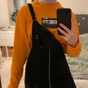 Orange t-shirt från Carlings med snyggt tryck på. Använd ett fåtal gånger, avklippt nedtill med fortfarande lång som en vanlig tröja. Köparen står för frakt!