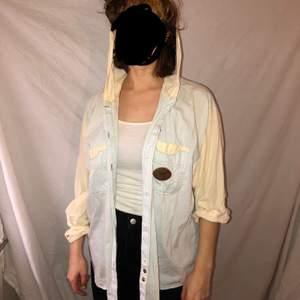 En skitmysig skjorta med en hoodie på som jag köpte i jaa förra vintern. i ljust gult och blått blockfärgat. Frakt på 50 kr tillkommer
