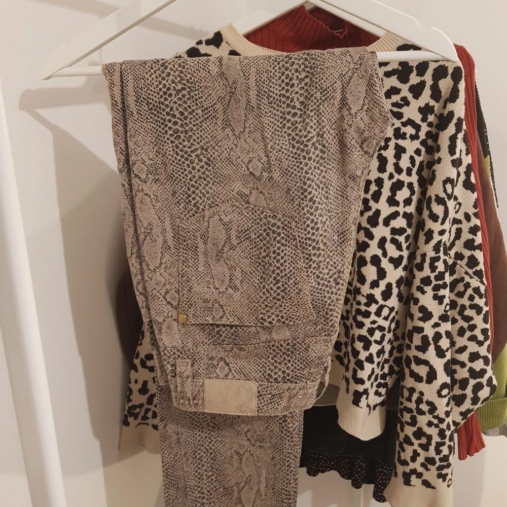 Sköna byxor från märket cappuccini. Fint tryck med snakeprint och dragkedjedetaljer på fickorna. Rak modell med normal midja. Är en perfekt längd på mig som är 169 cm. . Jeans & Byxor.
