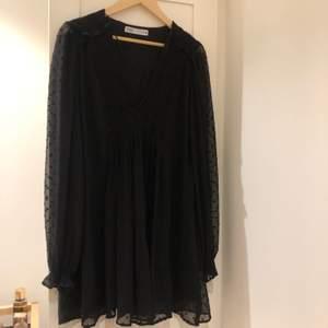 Svart klänning från Zara med långärmat prickigt mönster. Ganska kort klänning, men väldigt fin! Användt bara en gång. Storlek L men skulle säga att den passar mer som M/L. Köparen står för frakt!