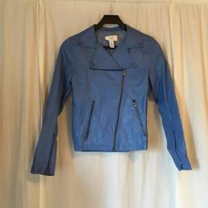 Blå jacka i fakeskinn från Issue 1.3. Två fickor med dragkedja framtill. Jackan stängs med både knäppning och dragkedja.