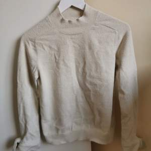 Jättefin beige stickad tröja med svagt glitter från Mango. Små knytningar vid armarna. Knappt använd. Storlek S