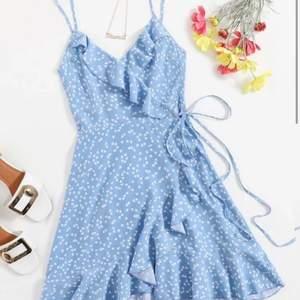 En blå klänning med små vita hjärtan över hela, ganska svår att knyta men superfin när man får till det. Aldrig använd. Frakt avgörs av vikten
