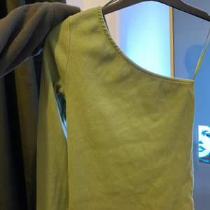 En grön enarmad tröja från Gina tricot i strl xs. Köpt för 250 kronor. Säljer för 100 kronor + frakt. (Färgen på plagget syns bäst på bild två.)