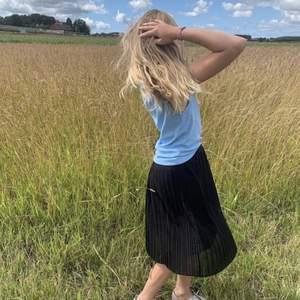 Svart kjol med Knälång längd, en resår midja, en inre underklänning och en veckad design. 130-140 är storleken men jag har storlek 146-152 och den passar fortfarande och jag är 153😊 bara att den blir liteeee kortare