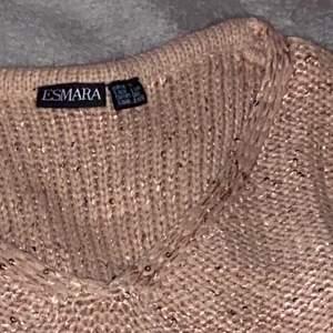 En stickad tröja i begie färg med palietter som inte har används