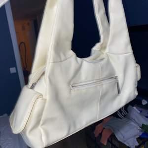 Väskan är 38 cm på brädden och 16 cm på längden.Väskan är i fint skick.Den är lite mer vit/beige
