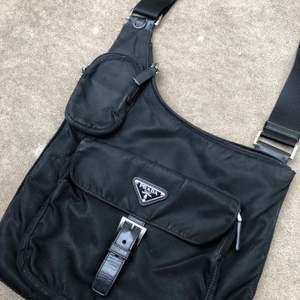Fett snygg väska från prada. Köpt begagnad för 3600kr. Den mindre fickan passar perfekt för att tex ha cigg i.  Zippern har lossnat på ena sidan men tror det går att laga! Skriv gärna om du har frågor eller vill ha fler bilder! Frakt ingår i priset:)