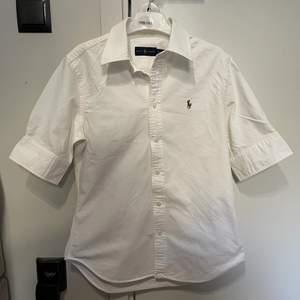 """Kortärmad skjorta från Ralph Lauren. Den är i storlek S och passar jättebra på mig som är i storlek S-M. Köpt på """"Stockholm Quality Outlet"""" för ett år sedan, har dock bara använt den i ett få tillfällen och jag har tagit hand om den väldigt bra. Jag kan mötas upp i Stockholm eller skicka den om köparen står för frakt."""