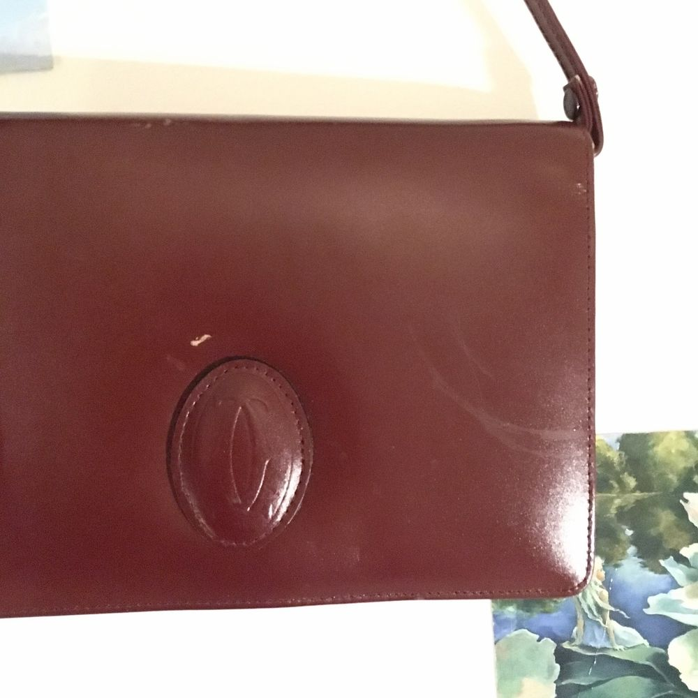 Supersnygg retrohandväska i dov blodröd färg (ser mer brun ut på foto än i verkligheten). Ger en cool retro vibe till vilken outfit som helst. Har några små skavanker på framsidan men inget som man tänker på när man har på sig den. Rymmer både plånbok och mobil. Ca 20x15x3. Accessoarer.