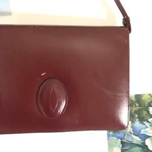 Supersnygg retrohandväska i dov blodröd färg (ser mer brun ut på foto än i verkligheten). Ger en cool retro vibe till vilken outfit som helst. Har några små skavanker på framsidan men inget som man tänker på när man har på sig den. Rymmer både plånbok och mobil. Ca 20x15x3