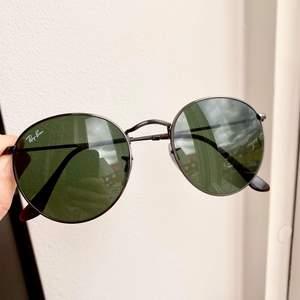 """Snygga Ray-Ban solglasögon i den populära modellen """"Round"""" storlek M. Grönt glas och båge i gun-metall. Nyskick!"""