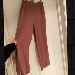kostymbyxor i silkesmaterial med resår i midjan fickor framtill