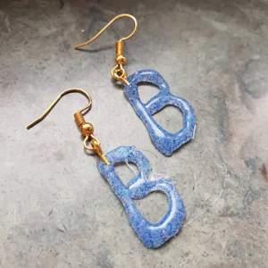 Handgjorda örhängen som är en bokstav av eget val. Guldiga krokar💛 Följ även min instagram om du vill se mer: siris_orhangen♡