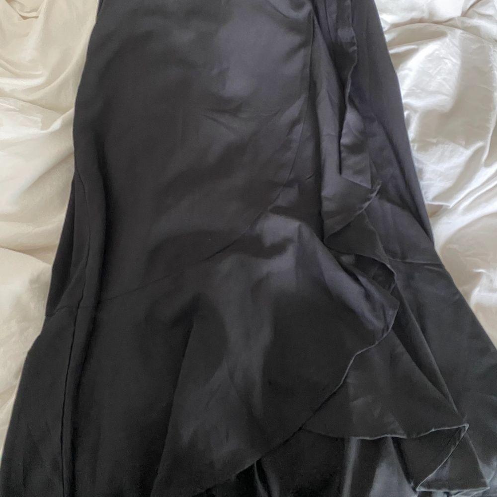 Svart kjol med volanger och knyt i midjan. Sparsamt använd. Frakt tillkommer🥰. Kjolar.