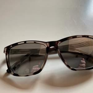 Snygga solglasögon med spegelreflekterande glas, lite silvrigt. Säljes för min hög med solglasögon är överflödig. Knappt använda, levereras med påse. Katt finns i hemmet