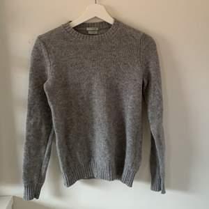 Grå stickad sweatshirt från United colors of benetton stickad med italienskt garn. Säljes för 200kr exklusive frakt,  aldrig använd och passar S