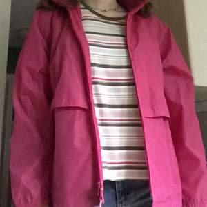 En rosa regn eller skaljacka som är secondhand, det finns en luva att fälla ut ur kragen.