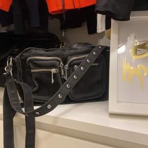 Svart noella väska från Two Angels. Den mindre storleken men rymmer fortfarande mycket! Den har tyvärr bara hängt bland alla andra väskor men den är väldigt snygg!😄 (köparen står för frakten, men kan mötas upp)