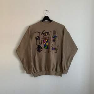 Vintage Sweatshirt med målningar. Den är i bra skick och Storleken är L men passar mer som M. Hänvisa till modellen som är 180cm