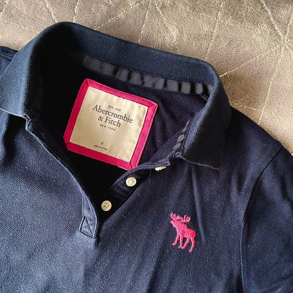 En mörkblå Abercrombie piké med rosa detaljer. I fint skick. Den är storlek M men är liten i storleken.. T-shirts.