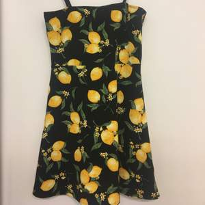 Svart klänning med citronmönster på. Använd en midsommarafton. Sitter fint på.