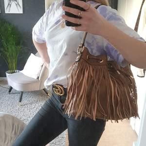 En brun handväska med snygga detaljer. Märket är di lauro och väskan är knappt använd så den är i mycket gott skick. Det finns flera innerfack i väskan samt stängning.