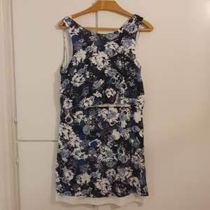 Blå blommig fin klänning med djup ringning i ryggen. Från Twist and Tango.