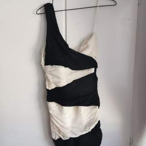 Svart och vit one shoulder, slinky blockklänning stretchigt material, från Jane Norman. Storlek 40. 75kr.