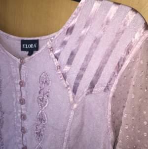 Söt rosa blus med snörning i ryggen💓. Kommer inte till användning hos mig tyvärr. Det står strl L men är en väldigt liten L.