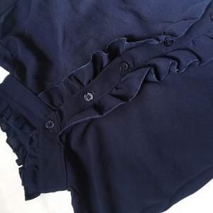 Cool skjorta med krås och volanger, knyt i ärmslut. Färgen är mörkblå och storleken passar mig som är 36-38! Väldigt bra skick! Kan mötas på/nära Lidingö alt. Skicka. Köparen betalar frakt :)