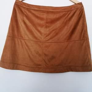 Beige/ljusbrun/tan kjol i mjuk tunn fejkmocka. Kort A-modell med dragkedja bak. Fint skick, använd men hittar inga fel. Storlek 16 UK, typ 42-44.