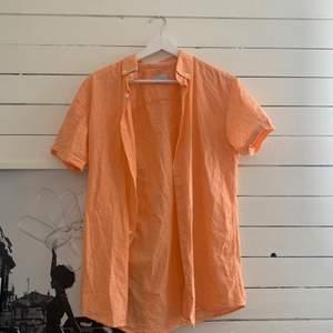 Orange kortärmad skjorta i storlek S från märket selenets homme, skulle säga att färgen inte tas upp 100% på kameran  utan att den är mer stark orange i verkligheten 🥰