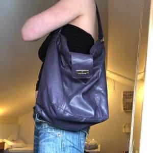 Lila väska i skinn (inte äkta tror jag). Lite slitningar på vissa ställen, skriv om ni vill ha bild!