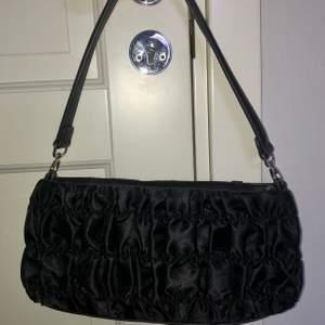 Svart snygg baguette väska från NAKD. I satin tyg med snyggt mönster. Rymlig och använd en gång.🌼