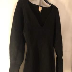 En svart stickad klänning, köpt från H&M trend. aldrig använd. Jätte fin modell vid bröstet.