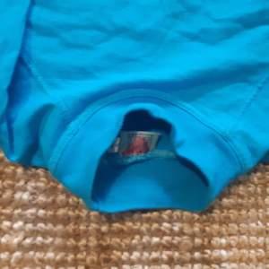 RETRO SWEATSHIRT typ oanvänd med hög krage i turkosblå färg. Ganska liten men kan passa en liten person. Skulle tippa att den är från 90 talet