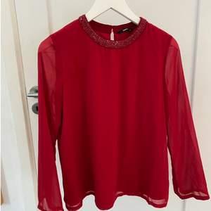 En röd blus från only! Den är i stl 34 och har små fina pärl detaljer vid kragen✨❤️