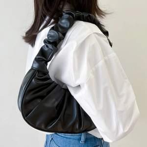 """frakt ingår i pris! skitsnygg svart """"skrynklig"""" väska, helt oanvänd. försluts med knapp."""