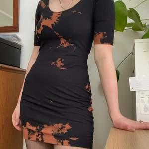 En svart tajt figurnära / figursydd klänning, blekt med tie-dye (batik) metod i ett häftigt mönster. Den är lika djup i ryggen som framtil så den går att ha åt båda håll. Den oranga färger skulle jag beskriva som rostorange. Lappen är borta så storlek vet jag ej men den passar mig som vanligtvis har M. Jag tror dock att den passar något mindre och något större eftersom tyget är stretchigt.