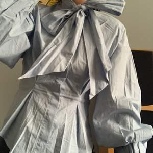 Fin, classy, ljusblå skjorta med rosett knytning i halden. Från H&M storlek 34. Använd ett få tal gånger och är i fint skick. Säljes pga inte riktigt min stil längre tyvärr. Frakt tillkommer om den ska skickas.