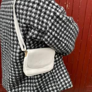 Vit, liten handväska med olika fack inuti