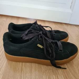Svarta Puma skor med brun platform sula. Skosnörena är i siden.
