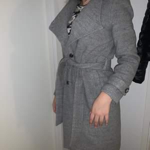 En jättefin grå kappa! Nyskick och säljer pga fick 2 likadana i födelsedagspresent!