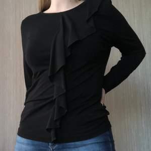 En tröja i tunt, lätt transparent tyg med volang framtill 😊 Storlek S, normal passform. Filippa K sheer frill top 🌷