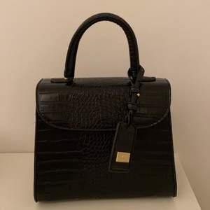 En svart handväska i krokodil skinn imitation från LYDC London inköpt på Zalando med gulddetaljer. Väskan har ett klicklås och ett innerfack med dragkedja. Ett tillhörande band medföljer samt dustbag. I toppskick då den använts knappast. Inköpt för 500 kr