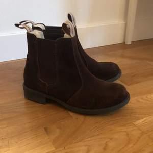 Ett par nästintill oanvända skor från märket Shepherd i storlek 37. Jag har ofta 36,5 så dessa skor passar bra! De är i brun mocka och har en gosig och fluffig insida. Paketet kan postas, men då får du stå för frakten.