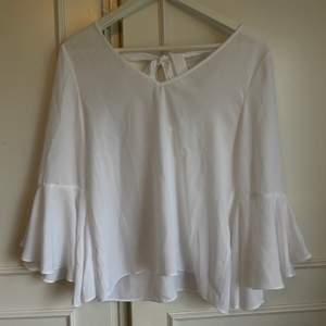 En vit blus med lite kortare ballongärm. Den har även en fin knytdetalj i ryggen. Endast provad så i nyskick.