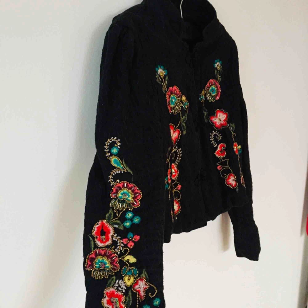 Black jacket with beautiful ornaments . Jackor.