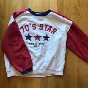 """Vit sweatshirt med röda ärmar och blåa detaljer. """"70s star always shine"""". Stora mysiga armar, skön inuti. Oversized modell, passar Xs-M"""
